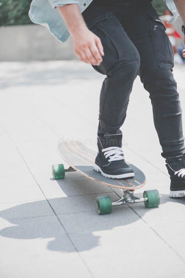 Feche acima do skater& x27; pés de s na equitação do longboard na rua dentro fora imagens de stock
