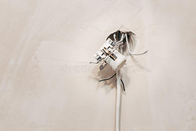 Feche acima do soquete aberto perigoso com fios de projeção na parede Conceito da segurança foto de stock royalty free