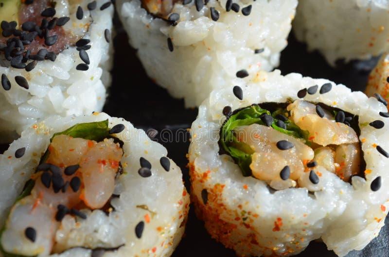 Feche acima do sushi polvilhado com as sementes de sésamo pretas imagens de stock royalty free