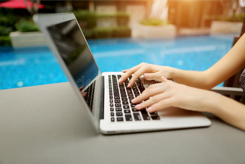 Feche acima do teclado da pressão de mãos da mulher na piscina do dia ensolarado do portátil imagens de stock