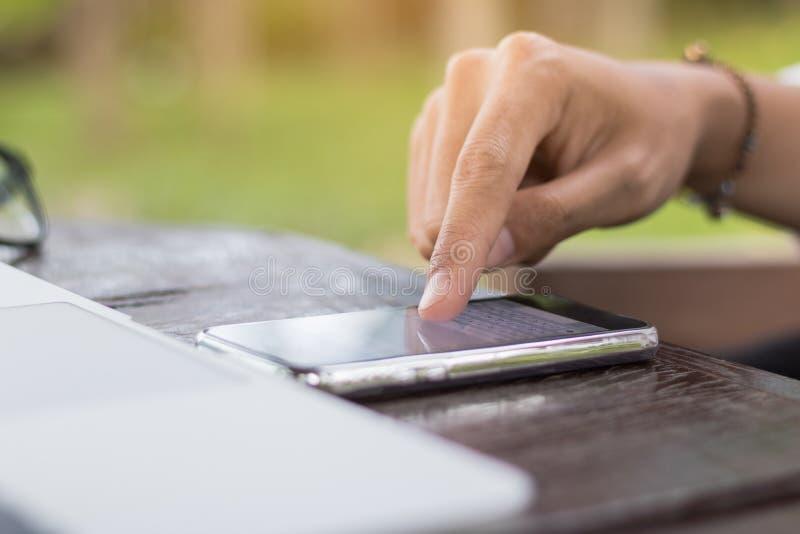 Feche acima do telefone celular do uso da mão da mulher com o portátil na cafetaria fotografia de stock
