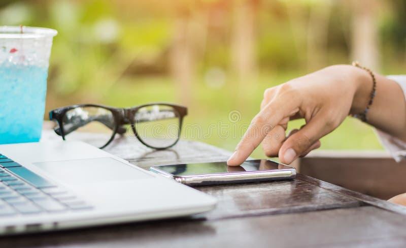 Feche acima do telefone celular do uso da mão da mulher com o portátil na cafetaria fotos de stock royalty free