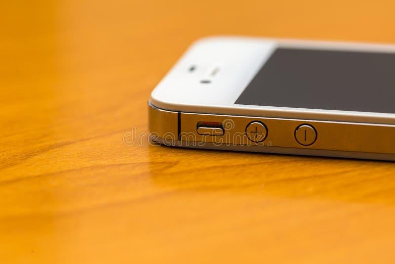 Feche acima do telefone celular que encontra-se na tabela de madeira foto de stock royalty free