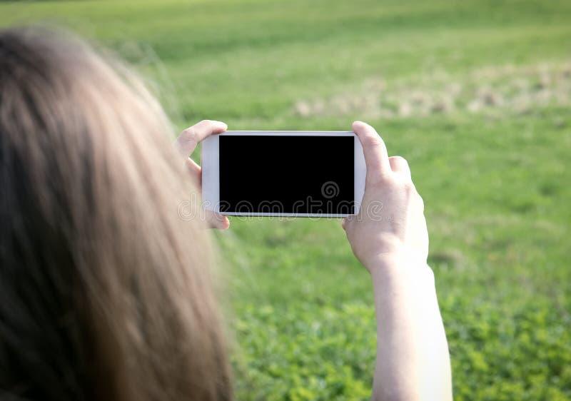Feche acima do telefone de pilha da terra arrendada das mãos do ` s das mulheres fotos de stock