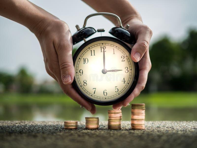 Feche acima do tempo de armazenagem da mão com a pilha de moedas, valor de época do conceito do dinheiro no tema da finança do ne fotografia de stock