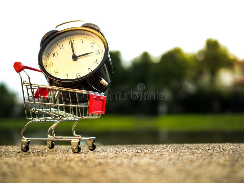 Feche acima do tempo do alarme no carrinho de compras, comprando o conceito do tempo fotografia de stock royalty free