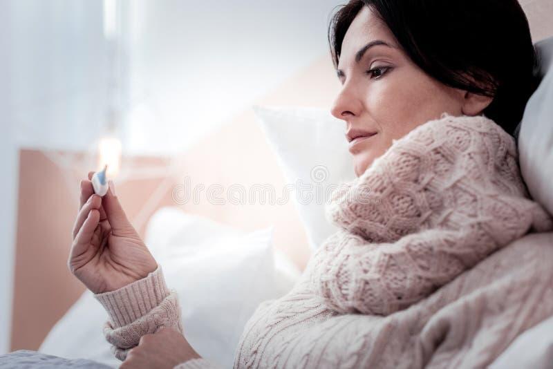Feche acima do termômetro calmo da terra arrendada da mulher nas mãos imagem de stock royalty free