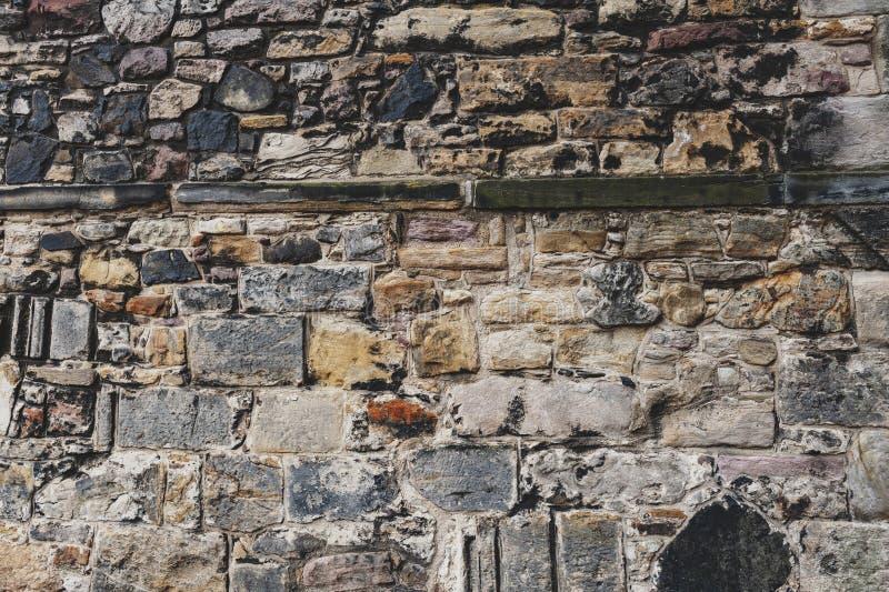 Feche acima do teste padrão dos detalhes da textura do fundo da parede de tijolo de pedra na construção antiga da fortaleza da ar imagens de stock
