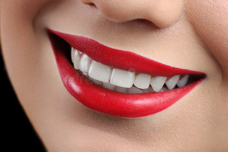 Feche acima do tiro colhido de um sorriso perfeito de uma mulher labiada vermelha imagem de stock royalty free