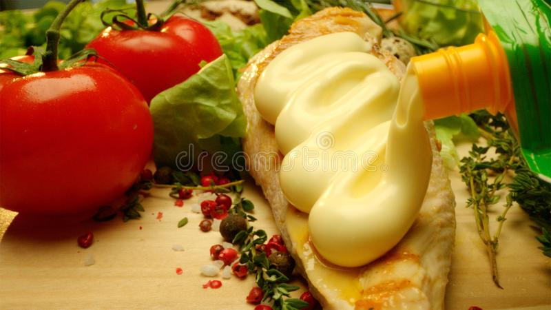 Feche acima do tiro comercial do peito de frango grelhado delicioso coberto com a maionese com verdes frescos e especiaria imagem de stock