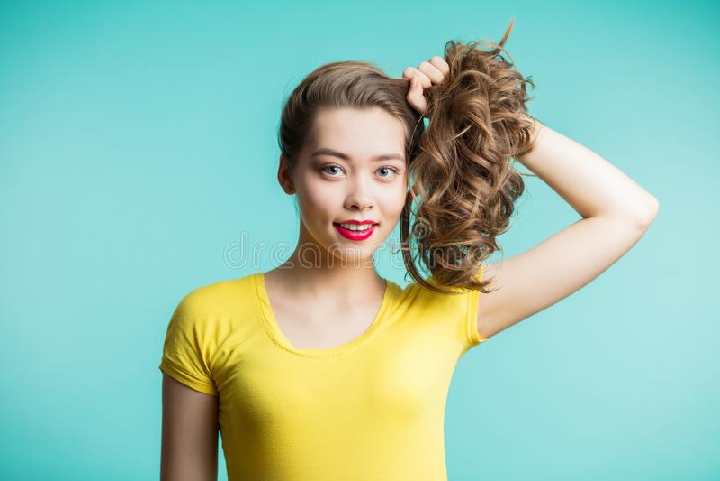 Feche acima do tiro da jovem mulher à moda que sorri contra o fundo azul O modelo fêmea bonito recolheu as mãos e os olhares do c imagem de stock
