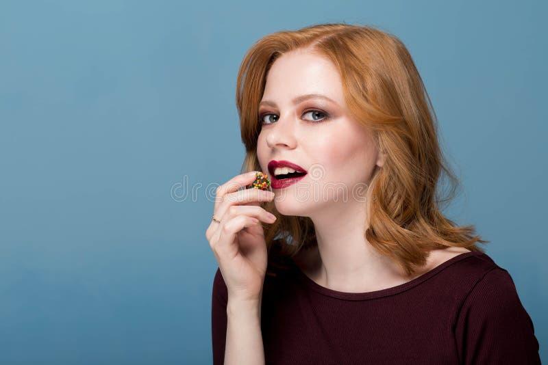 Feche acima do tiro da jovem mulher à moda do ruivo contra o fundo azul O modelo fêmea bonito come uns doces redondos imagens de stock