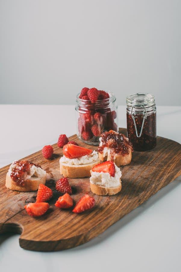 feche acima do tiro da placa de corte com doce de morango em uns frascos e em uns sanduíches com queijo creme e doce imagem de stock