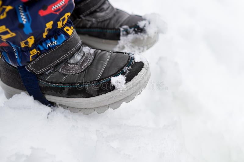 Feche acima do tiro de botas de neve das crianças Footware do inverno Menino que está na neve, detalhe das sapatas fotografia de stock