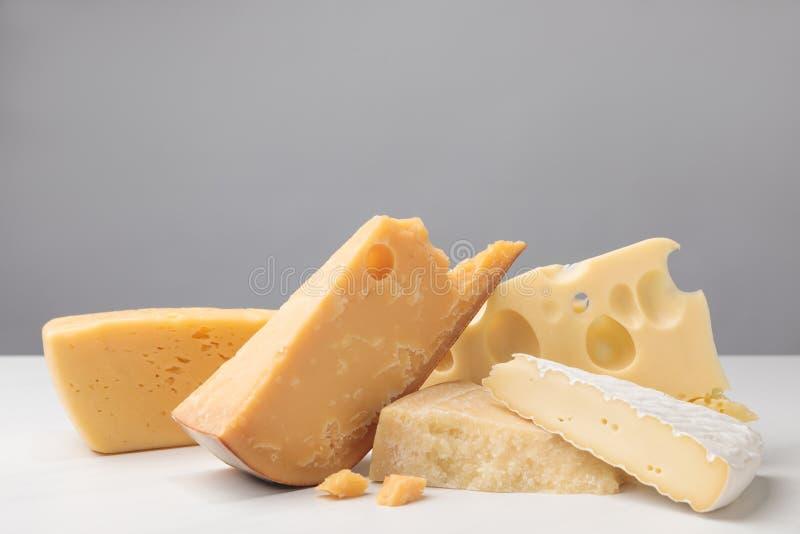 Feche acima do tiro de tipos diferentes de queijo no cinza foto de stock