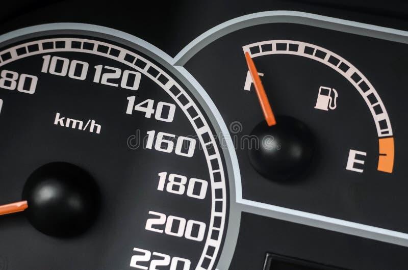 Feche acima do tiro de um medidor de velocidade e de um calibre de combustível em um carro imagem de stock