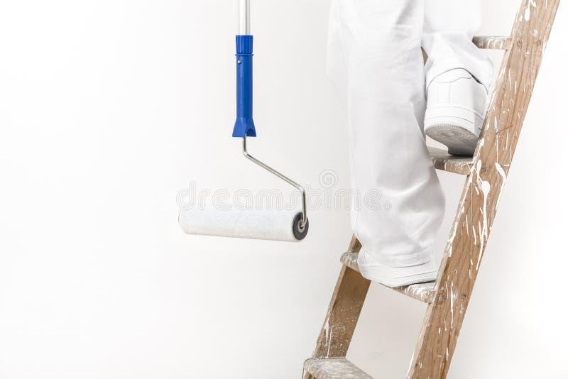 Feche acima do tiro do homem do pintor no trabalho que escala uma escada com dor imagens de stock