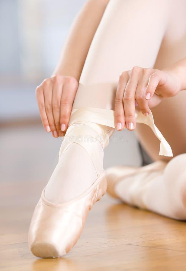 Feche acima do tiro dos pés da bailarina que atam os pointes imagens de stock royalty free