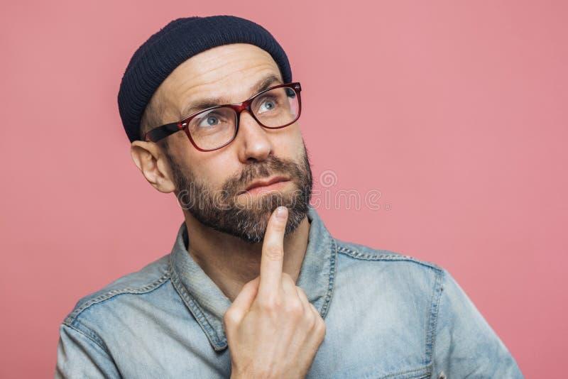 Feche acima do tiro do homem farpado de vista agradável com expressão pensativa, mantenha o dedo no queixo, olhe pensativamente a imagem de stock royalty free