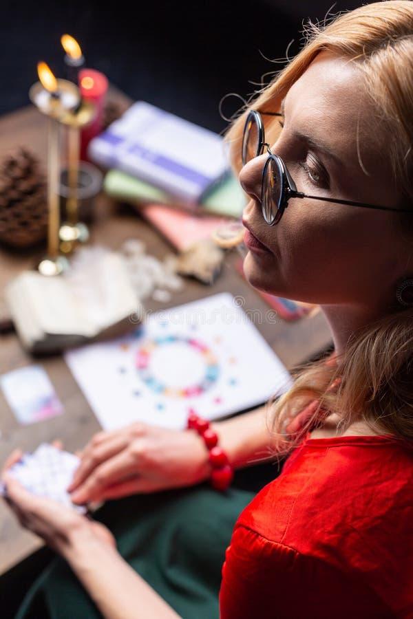 Feche acima do trabalho ocupado do sentimento maduro bonito do astrologist em casa fotos de stock