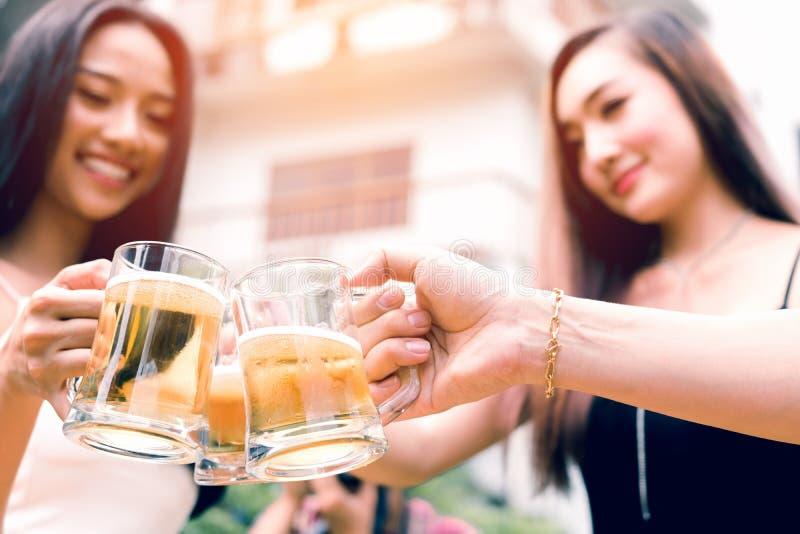 Feche acima do vidro de cerveja asiático do tim-tim do adolescente no feriado no jardim ho fotografia de stock royalty free