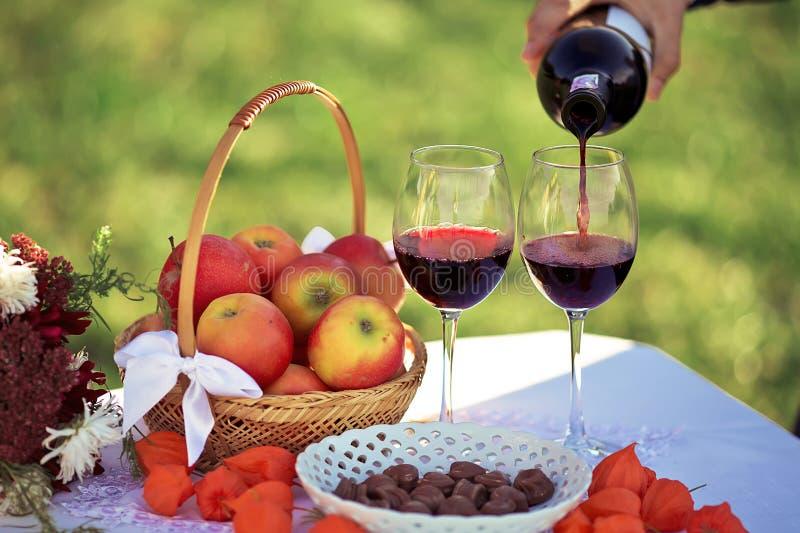Feche acima do vinho tinto que está sendo derramado da garrafa ao vidro, piquenique na natureza, uma cesta das maçãs, doces de ch imagens de stock royalty free