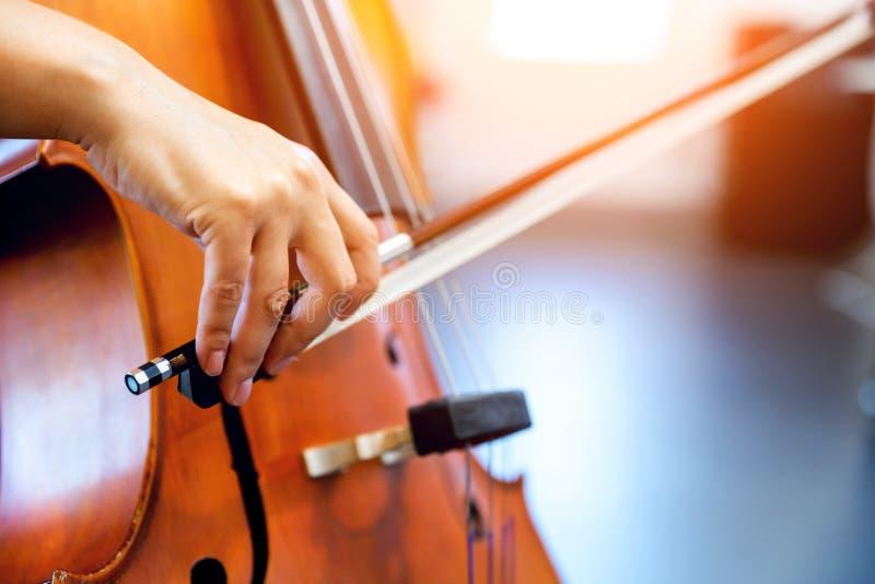 Feche acima do violoncelo com curva nas mãos foto de stock