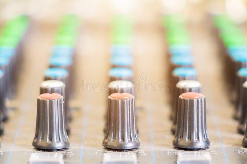 Feche acima do volume que ajusta os botões velhos no controlador audio do misturador na sala de comando imagem de stock