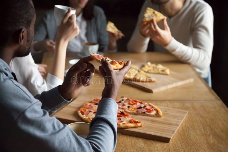 Feche acima dos amigos diversos que comem a pizza para fora foto de stock