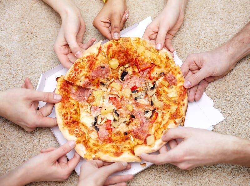 Feche acima dos amigos felizes que comem a pizza em casa fotos de stock royalty free