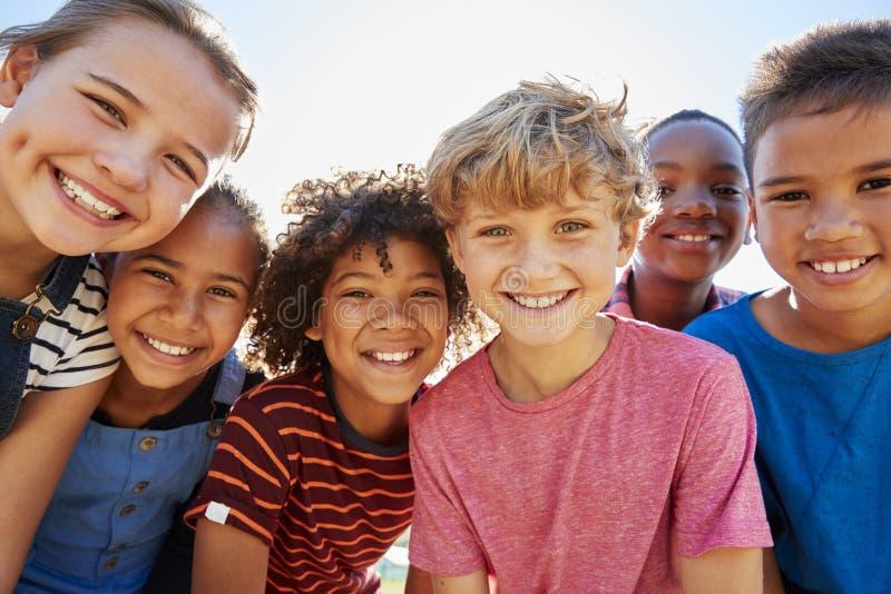 Feche acima dos amigos pre-adolescentes em um parque que sorriem à câmera imagem de stock