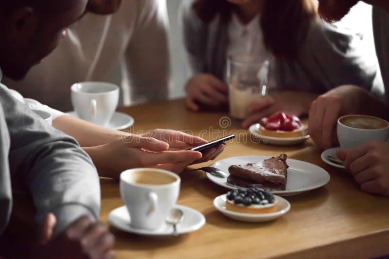 Feche acima dos amigos que olham imagens no smartphone no café fotos de stock royalty free