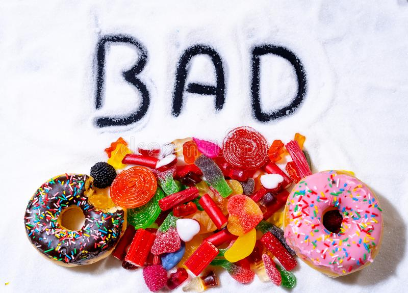 Feche acima dos anéis de espuma coloridos dos doces dos doces com o mau escrito no açúcar branco na dieta insalubre da criança imagens de stock royalty free
