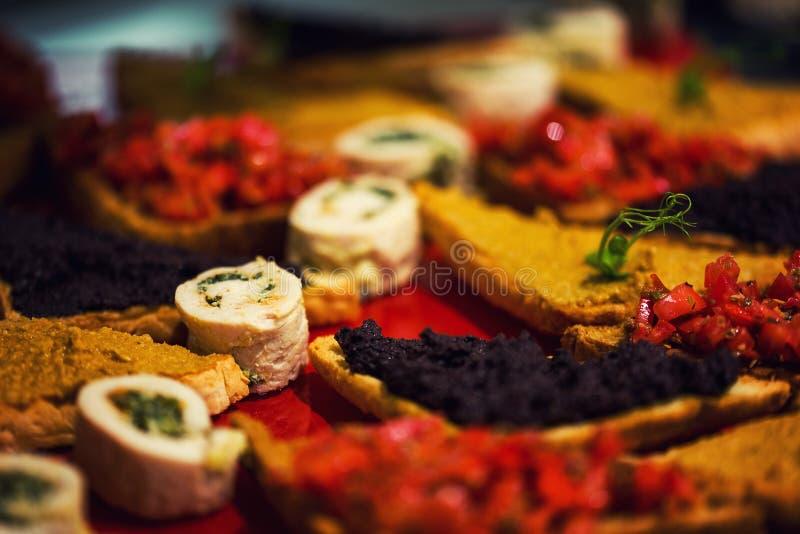 Feche acima dos aperitivos italianos do tomate saboroso saboroso, ou do bruschett foto de stock