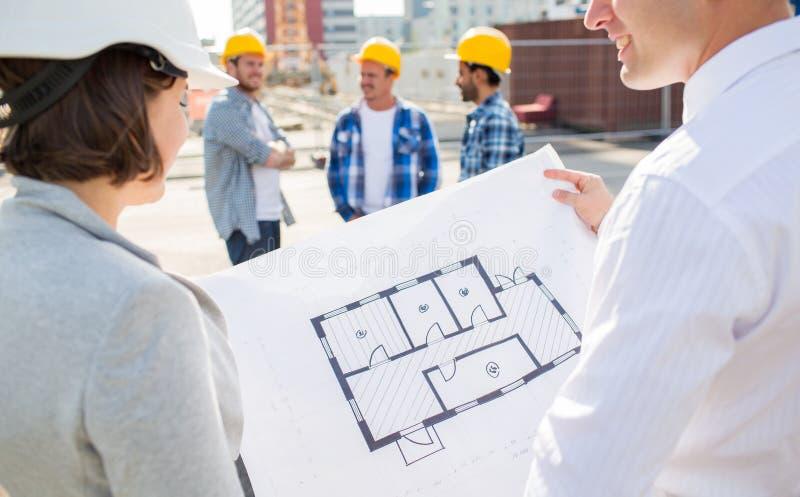 Feche acima dos arquitetos com o modelo na construção foto de stock royalty free