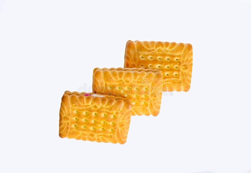 Feche acima dos biscoitos quadrados da forma enchidos com o creme branco e cor-de-rosa isolado fotografia de stock