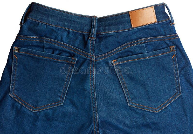 Feche acima dos bolsos traseiros em calças de brim foto de stock royalty free