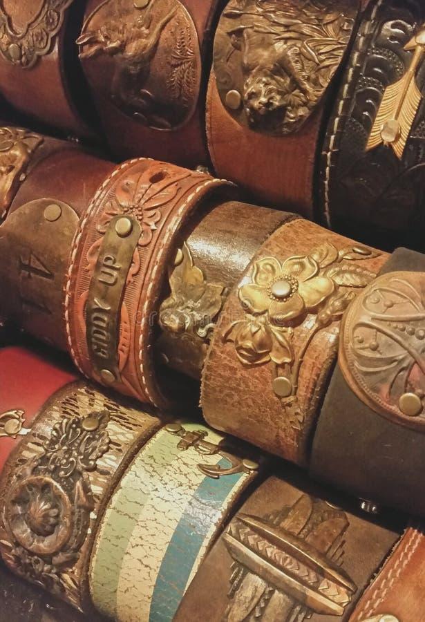 Feche acima dos braceletes de bronze e de couro feitos a mão fotografia de stock