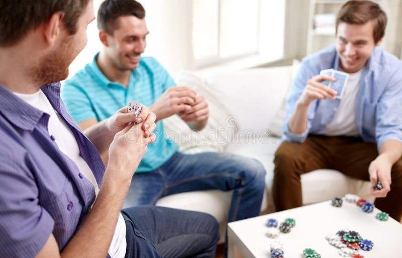 Feche acima dos cartões de jogo masculinos dos amigos em casa foto de stock