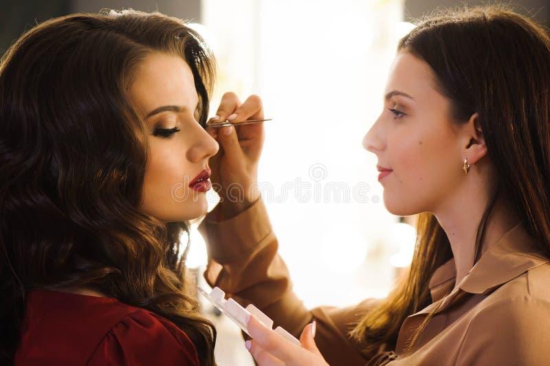 Feche acima dos chicotes de alongamento do estilista profissional para o cliente fêmea em um salão de beleza fotografia de stock royalty free