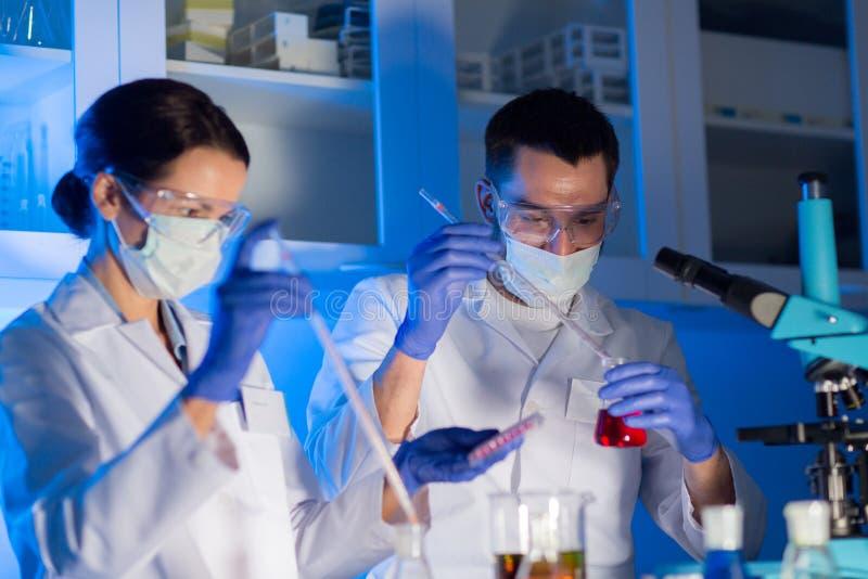 Feche acima dos cientistas que fazem o teste no laboratório imagens de stock