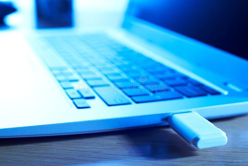Feche acima dos dados do computador que estão sendo transferidos do portátil a Portab fotografia de stock