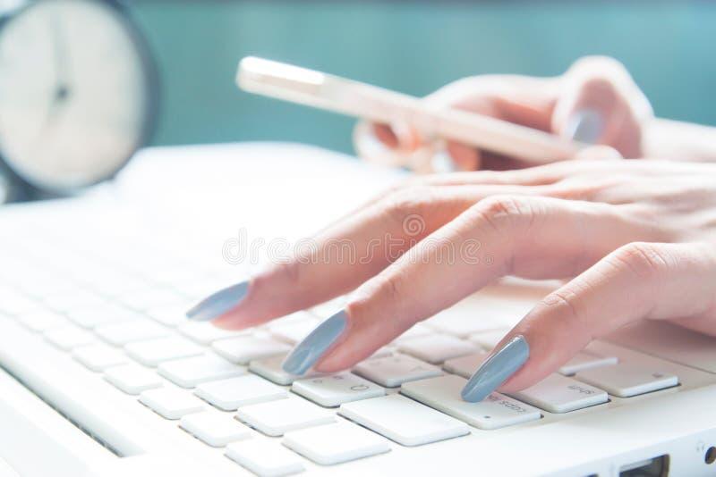 Feche acima dos dedos fêmeas usando o portátil e o dispositivo móvel, a mulher de funcionamento e a compra em linha fotos de stock royalty free