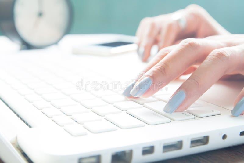 Feche acima dos dedos fêmeas usando o portátil, a mulher de funcionamento e a compra em linha imagens de stock
