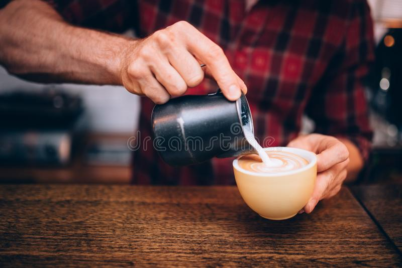 Feche acima dos detalhes de barman que trabalham na loja do café Leite de derramamento sobre o café e a criação do cappuccino fotografia de stock royalty free