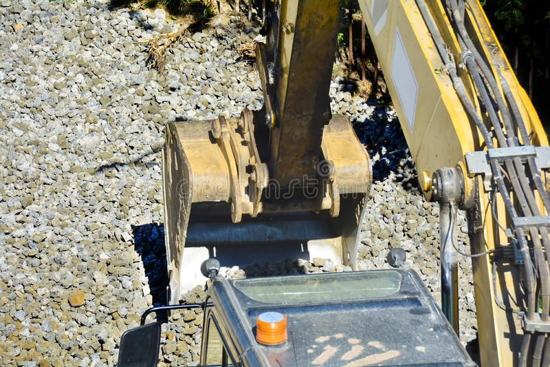 Feche acima dos detalhes de um funcionamento industrial da máquina escavadora em um canteiro de obras Cascalho dos níveis da cube imagem de stock royalty free