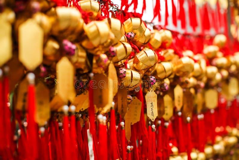 Feche acima dos devotos das fileiras que penduram sinos dourados da oração para abençoar em Wong Tai Sin Temple, Hong Kong foto de stock royalty free