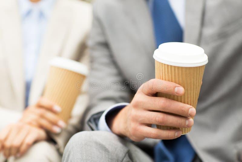 Feche acima dos executivos das mãos com copos de café imagem de stock royalty free