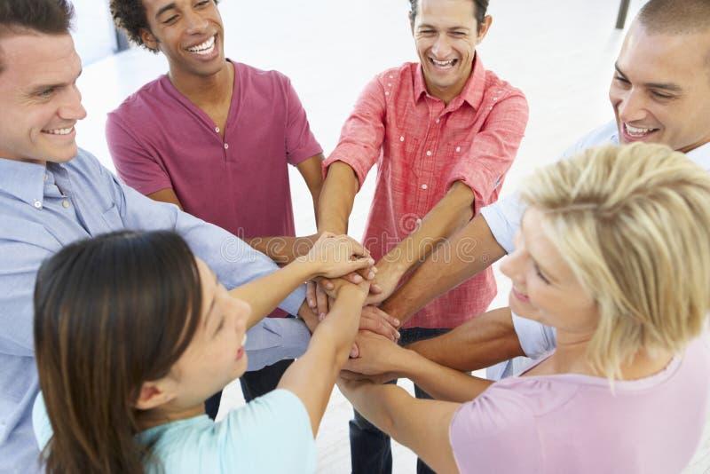 Feche acima dos executivos que juntam-se às mãos em Team Building Exercise fotografia de stock
