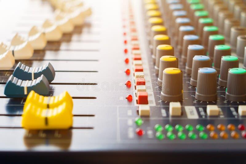 Feche acima dos Faders do volume do misturador sadio que ajusta o controlador dos botões na sala de comando fotografia de stock